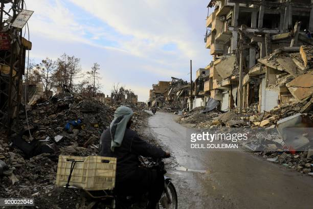 Syrian man drives a motorbike along a destroyed street in Raqa the former de facto capital of the Islamic State group on February 18 2018 / AFP PHOTO...
