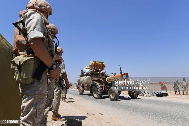 A Syrian man drives a tractor as members of Russian and Syrian forces stand guard at the Abu Duhur crossing on the eastern edge of Idlib province on...