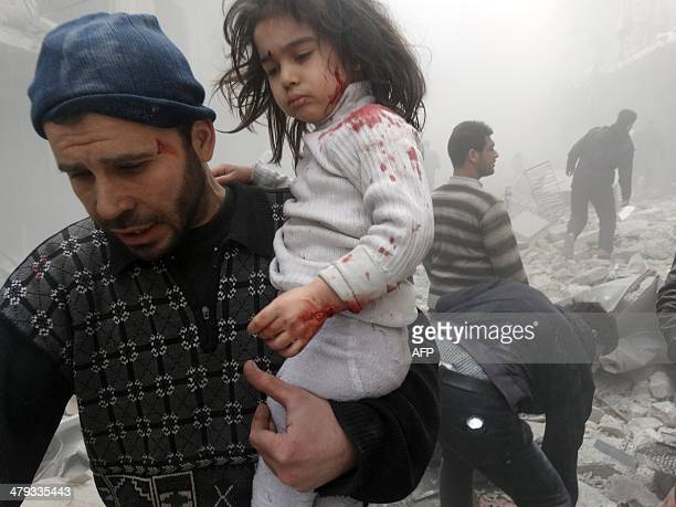 A Syrian man evacuates a child found in the rubble of a building reportedly hit by an explosivesfilled barrel dropped by a government forces...