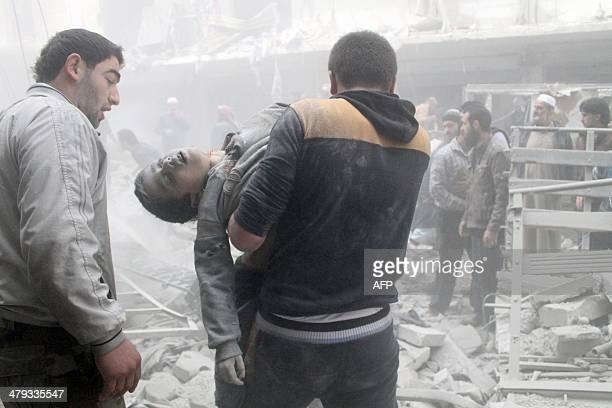 A Syrian man evacuates a child found in the rubble of a residential building reportedly hit by an explosivesfilled barrel dropped by a government...