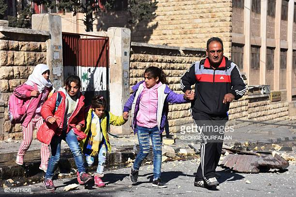A Syrian man evacuates children from a school reportedly hit by rebel rocket fire in the Furqan neighbourhood of the governmentheld side of west...