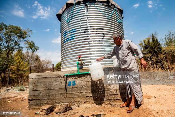Syrian man fills up water from a water tank, provided by humanitarian organisations, during a water outage in Syria's northeastern city of Hasakah on...
