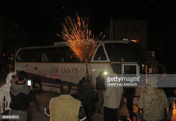 Syrian man fires into the air to celebrate as buses transporting Syrians evacuated from two besieged rebelheld towns of Madaya and Zabadani arrive in...