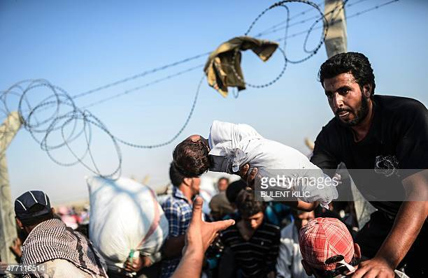 A Syrian man fleeing the war passes a child over border fences to enter Turkish territory illegally near the Turkish border crossing at Akcakale in...
