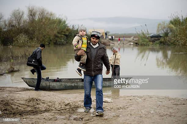 A Syrian man from Jisr alShughur carries his son as a family gets ready to board a boat to flee across the Orontes river to Turkey near the northern...