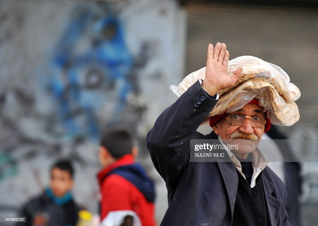 A Syrian man gestures after getting bread in the northern city of Aleppo on February 14, 2013. Syrian Foreign Minister Walid al-Muallem and opposition National Coalition chief Ahmed Moaz al-Khatib will make separate visits to Moscow for talks in the coming weeks, a top Russian diplomat said.