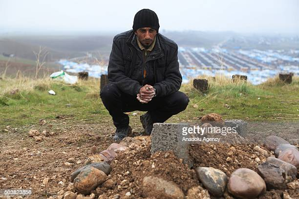 Syrian man has been forced to leave their homes because of the war in their country since 2011 prays in front of his son's grave at Kevirgosk Refugee...