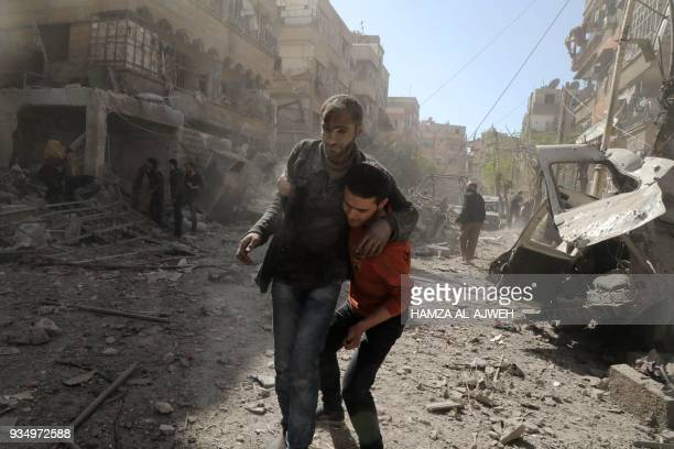 Syrian man helps evacuate an injured victim following Syrian government air strikes on the Eastern Ghouta rebelheld enclave of Douma on the outskirts...