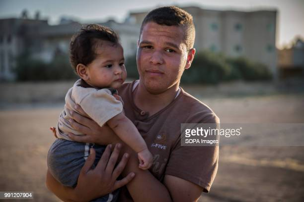 Syrian man holds his baby in a street in Mafraq There are about 14 million Syrian refugees in Jordan and only 20 percent are living in the refugee...
