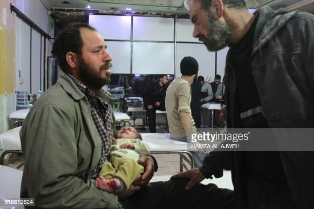 A Syrian man holds his infant who was rescued from under the rubble following air strikes on the rebelheld besieged town of Douma in the eastern...