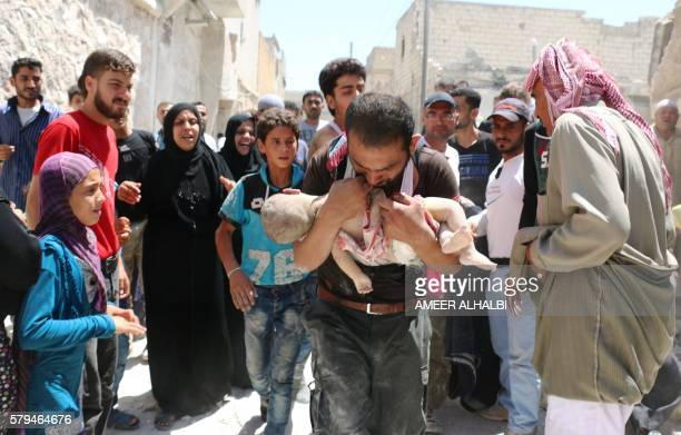 Syrian man holds the body of his child after it was taken from under the rubble of destroyed buildings following a reported air strike on the...