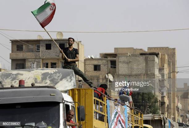A Syrian man holds the Iranian flag as a convoy carrying aid provided by Iran arrives in the eastern city of Deir Ezzor on September 20 2017 while...
