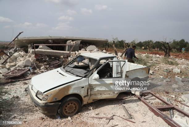 A Syrian man inspects a car wreck at the site of a damaged building reportedly hit during Russian airstrikes on the town of Taftanaz and its...