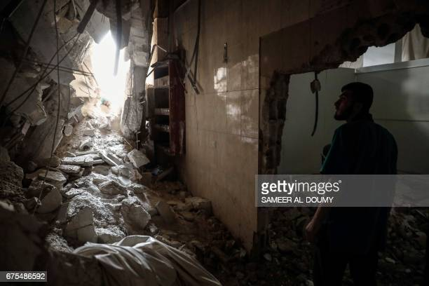 Syrian man inspects a hospital, damaged following an air strike a rebel-controlled town in the eastern Ghouta region on the outskirts of the capital...