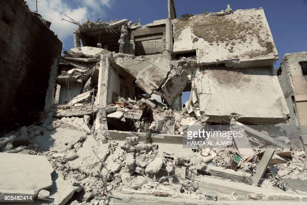 Syrian man inspects the damage of a buildings which was destroyed earlier in regime air strikes, in the rebel-held besieged town of Douma in the...