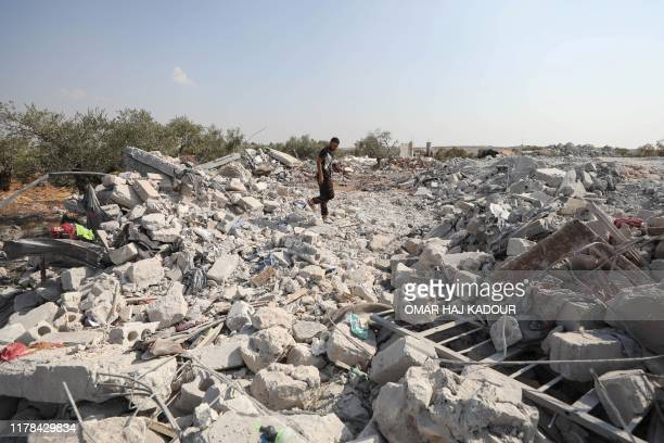 Syrian man inspects the site of helicopter gunfire which reportedly killed nine people near the northwestern Syrian village of Barisha in the Idlib...