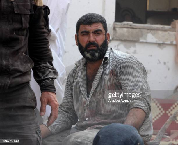 Syrian man is seen near the wreckage of a building after airstrikes hit Khan Sheikhun town of Idlib Syria on September 21 2017