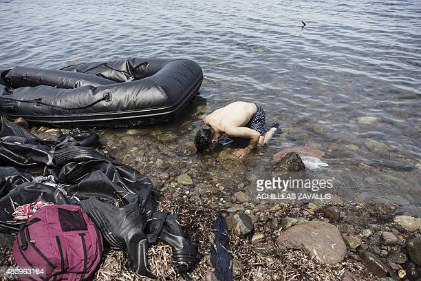 Syrian man kisses the ground moments after arriving on the shores of the Greek island of Lesbos after crossing the Aegean sea from Turkey to Greece...