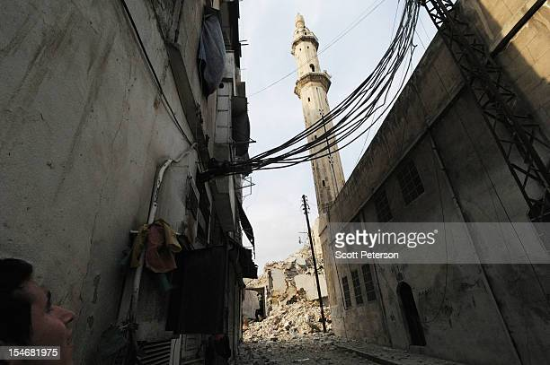 Syrian man looks upon a damaged mosque and sniper lane as the intense human and material cost grows from three months of intense fighting against...
