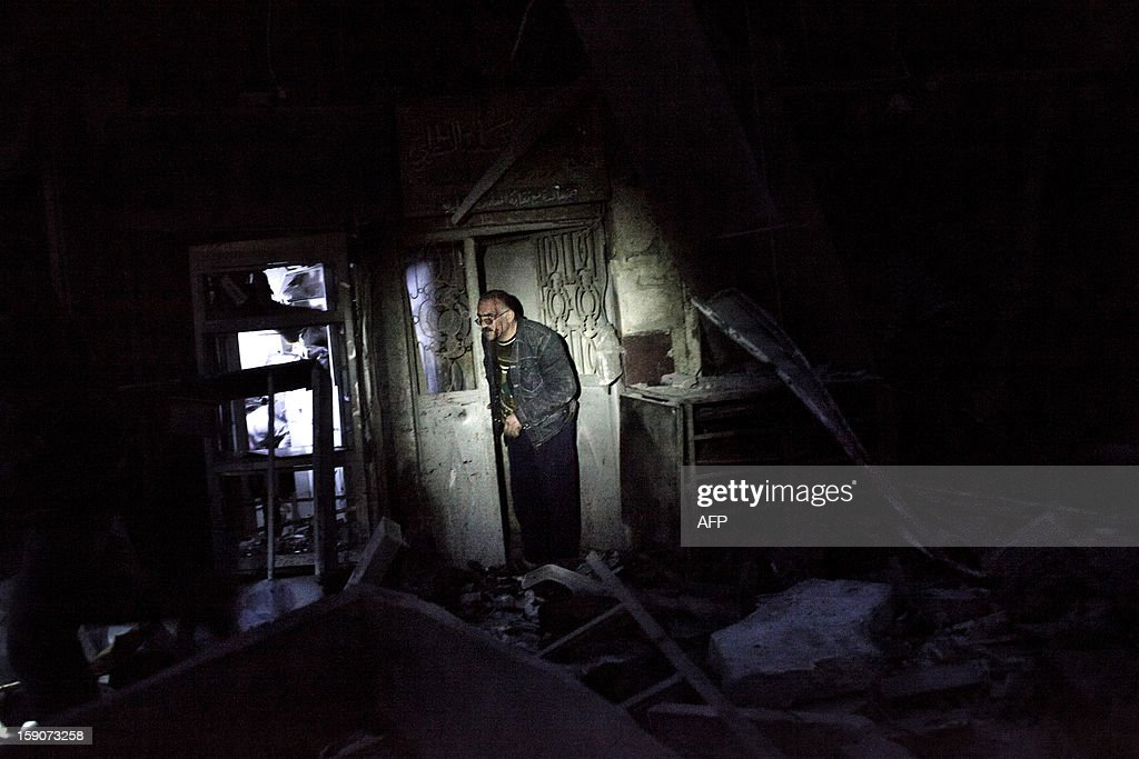 A Syrian man makes his way out of a destroyed building after it was targeted by a missile in the al-Mashhad neighbourhood in the city of Aleppo on January 7, 2013. The United Nations recently denounced a 'proliferation of serious crimes including war crimes' in Syria, as ever more horrifying images and videos emerge from the country.