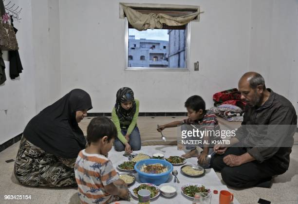 Syrian man Mehdi Haymur and his family wife Raifa son Saad daughter Inas and son Mohamad share a meal in Afrin on May 26 2018 Displaced from their...