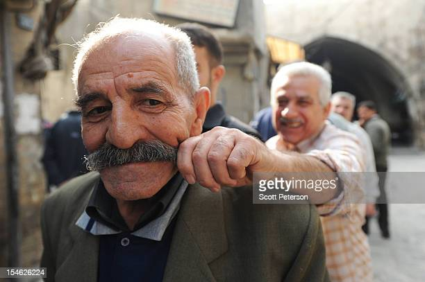 Syrian man playfully pulls the mustache of another as they wait in line to buy bread from a rebel delivery after three months of intense government...