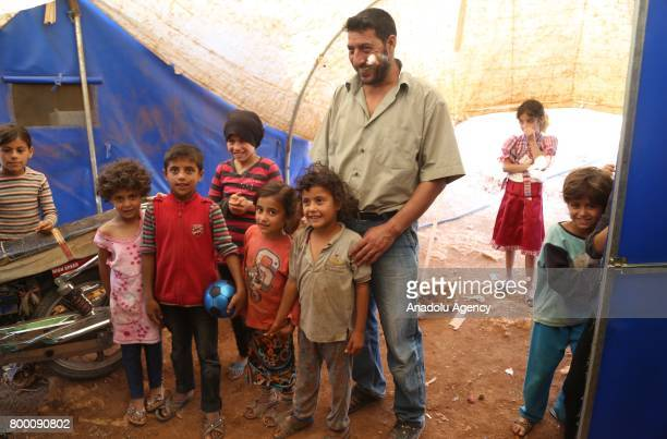 Syrian man poses inside a tent with kids during Muslim's holy month of Ramadan in Idlib Syria on June 23 2017 Ahead of Eid al Fitr Syrian people who...