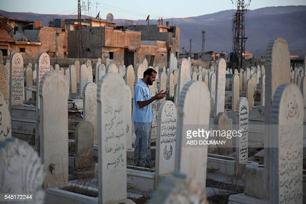 A Syrian man prays at a grave of his father in the rebelheld town of Douma east of the capital Damascus on July 6 the first day of the Eid alFitr...
