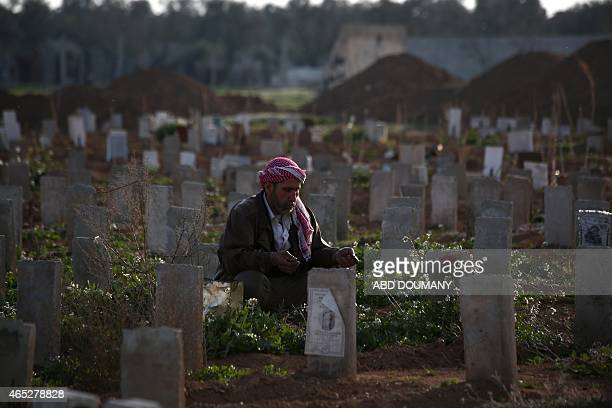 A Syrian man prays over the grave of his son who was killed during shelling at a cemetery in the rebelheld Damascus suburb of Douma on March 5 2015...