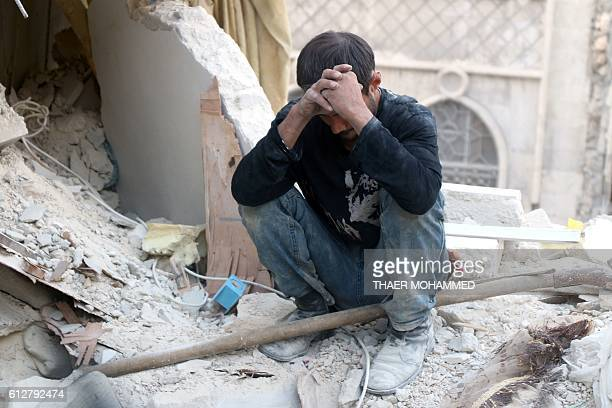 A Syrian man reacts as he sits on the rubble of destroyed buildings following a government forces air strike on the rebelheld neighbourhood of Bustan...