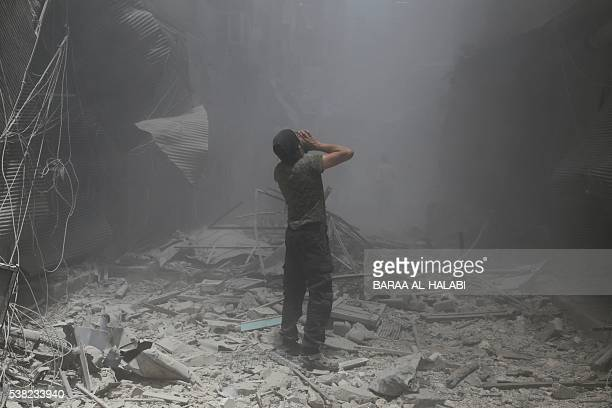 Syrian man reacts following a reported air strike by Syrian government forces in the rebelheld neighbourhood of Bustan alQasr on June 5 2016 / AFP /...
