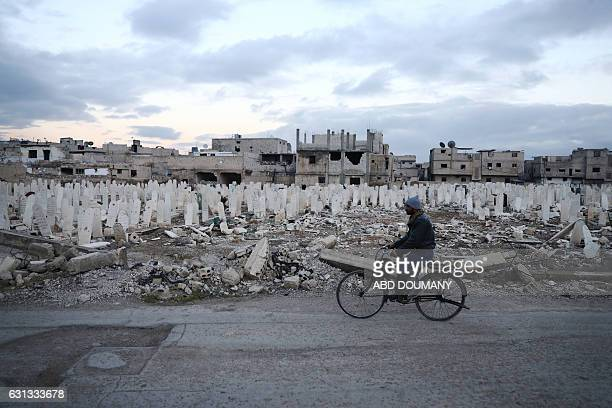 Syrian man rides a bicycle in the rebelheld town of Douma on the eastern outskirts of the capital Damascus on January 9 2017 / AFP / Abd Doumany