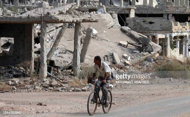 Syrian man rides a bicycle past destroyed buildings in an opposition-held neighbourhood of the southern city of Daraa on October 2, 2018.
