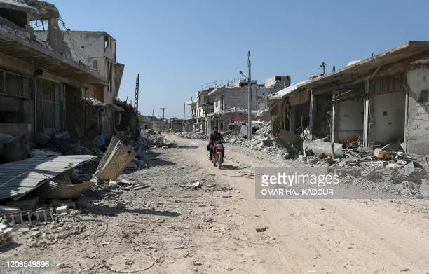 Syrian man rides a motorbike on a rubble-covered street in Afis town which has sustained widespread destruction due to heavy fighting and air-strikes...