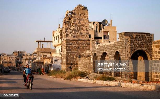 Syrian man rides a motorcycle while carrying a gas cylinder as he drives past the Omari mosque in a rebel-held area in the southern Syrian city of...