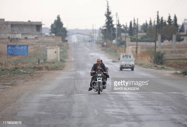 Syrian man rides a motorscycle on October 25, 2019 through a deserted road, exiting the border town of Tal Abyad in northeastern Syria, seized by...