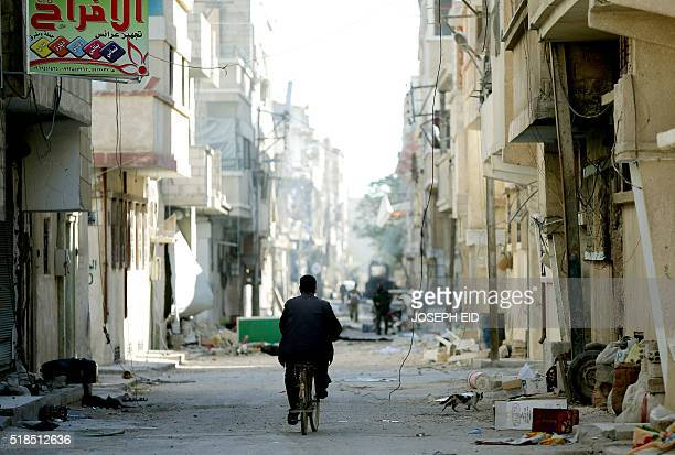 Syrian man rides his bicycle on a street on March 31 2016 in the modern town adjacent to the ancient Syrian city of Palmyra Syrian troops backed by...