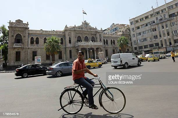 A Syrian man rides his bicycle past Hejaz train station in the Syrian capital Damascus on September 5 2013 AFP PHOTO / LOUAI BESHARA