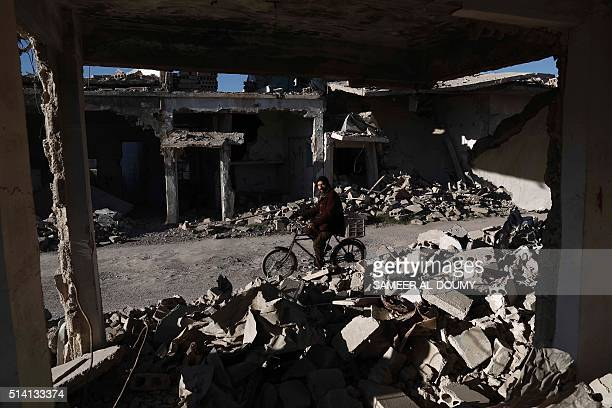 Syrian man rides his bicycle past the rubble of destroyed buildings on March 7 in the rebelheld town of Douma on the outskirts of the capital...