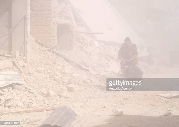 Syrian man rides his bicycle through smoke after Assad Regime's airstrike over civilians in residential areas at the Douma town of Eastern Goutha in...