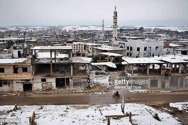 Syrian man rides his motorbike past damaged buildings covered with snow on December 18 in a rebelheld district of Homs / AFP / MAHMOUD TAHA