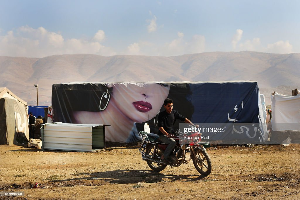 A Syrian man rides his motorcycle in a makeshift camp occupied by Syrian refugees in the Bekaa Valley, close to the border with Syria on November 11, 2013 in Majdal Anjar, Lebanon. As the war in neighboring Syria drags on for a third year, Lebanon, a country of only 4 million people, is now home to the largest number of Syrian refugees who have fled the conflict. The situation is beginning to put huge social and political strains on Lebanon as there is currently no end in sight to the war in Syria.