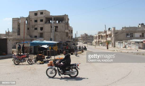 A Syrian man rides his motorcycle in Khan Sheikhun on April 7 2017 near the area of a suspected chemical weapons attack earlier this week on the...