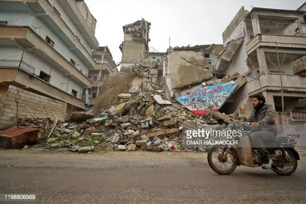Syrian man rides his motorcycle past a damaged building following an air strike by pro-regime forces on the rebel-held town of Ariha in the northern...