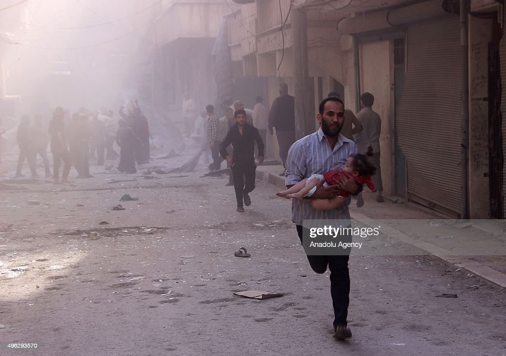 A Syrian man runs as he carries his injured kid after the Russian air strikes in Sukeri region of Aleppo, Syria on November 08, 2015.