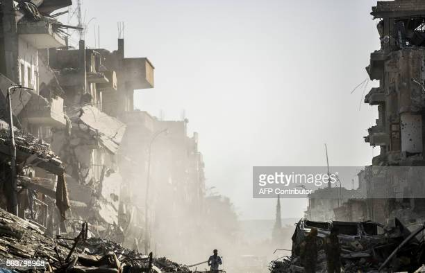 A Syrian man runs down a street in Raqa past destroyed vehicles and heavily damaged buildings on October 20 after a Kurdishled force expelled Islamic...