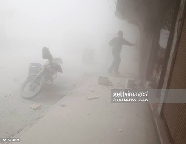 Syrian man runs for cover amid the dust and smoke following a reported government air strike on the rebel-controlled town of Hamouria, in the eastern...
