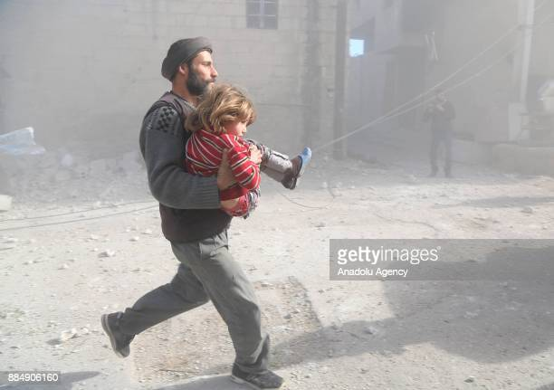 Syrian man runs with his daughter following the Assad regime's air strikes over residential areas in the deescalation zone in the Eastern Ghouta...