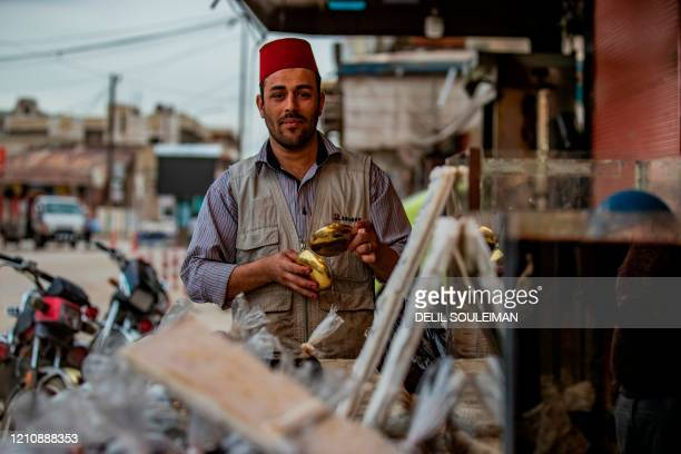 A Syrian man selling liquorice juice a traditional drink during Ramadan waits for customers outside his shop in the city of Qamishli in Syria's...