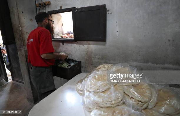 Syrian man sells bread in the town of Binnish in the country's northwestern Idlib province on June 9, 2020. - Syrians held a third day of rare...